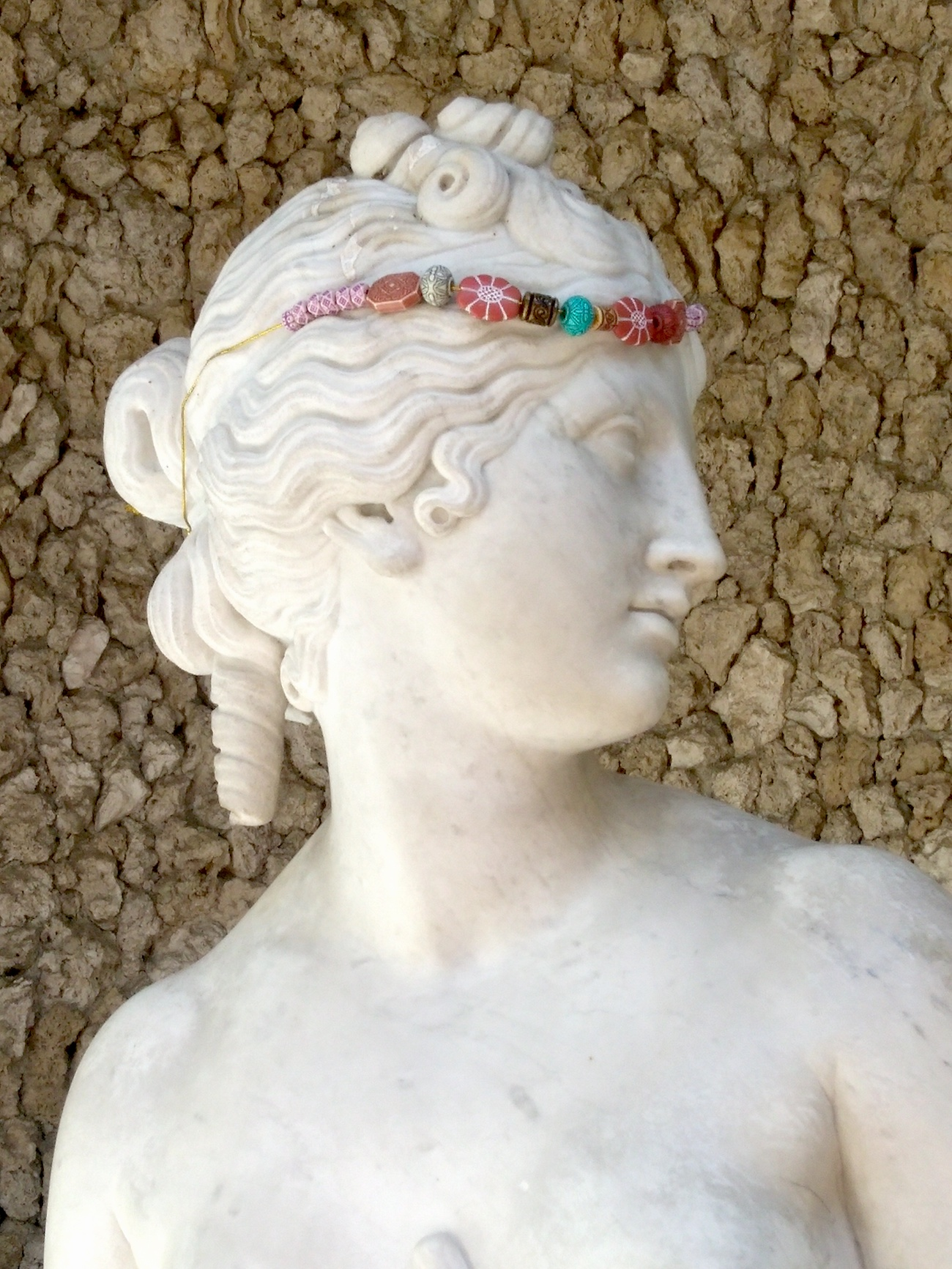 A marble statue of Venus with a beaded headband