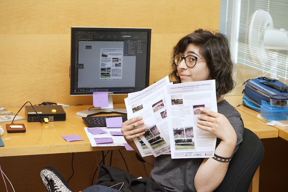 A young woman with short brown hair and glasses holds up several print newsletters while looking slyly at the viewer
