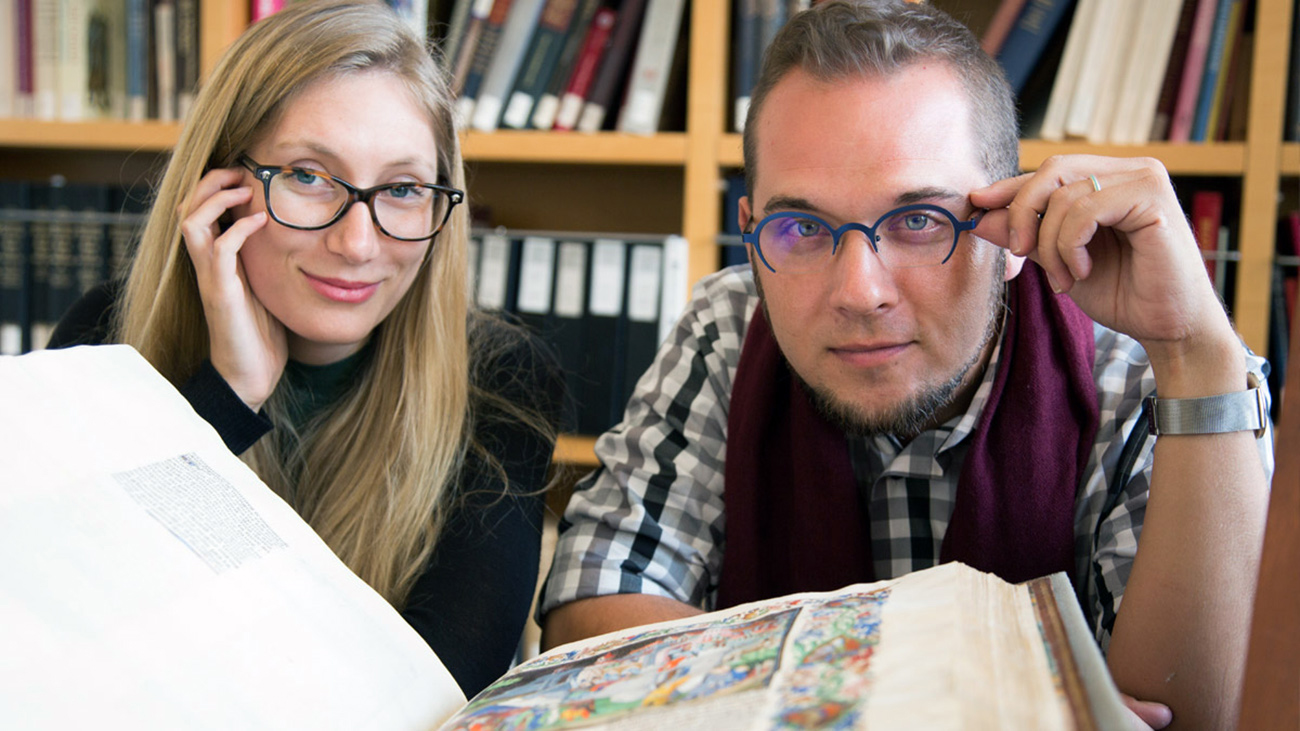 Two curators make eye contact with the view while an illuminated manuscript is open.