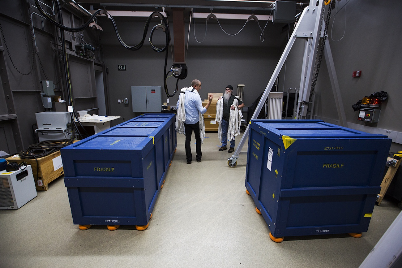 Wide-angle view of a large room with two large, deep-blue packing crates
