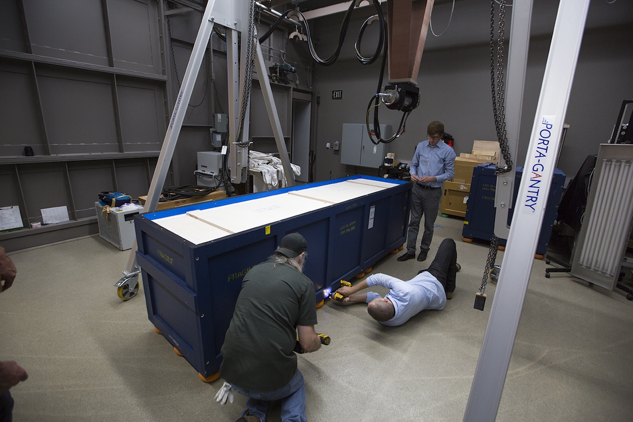 Three men use power tools to open a large, low, long packing crate painted deep blue