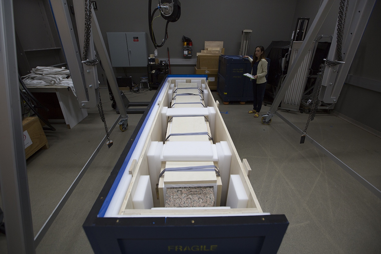 Overhead view of a partially opened packing crate containing a granite obelisk lying on its side, surrounded by packing materials