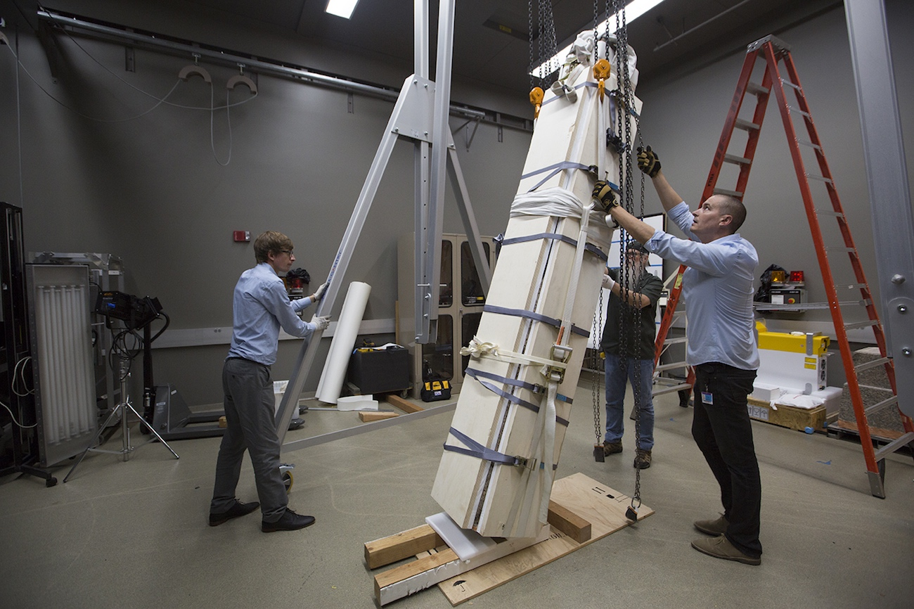 An obelisk, encased in packing materials, is hoisted to nearly upright position