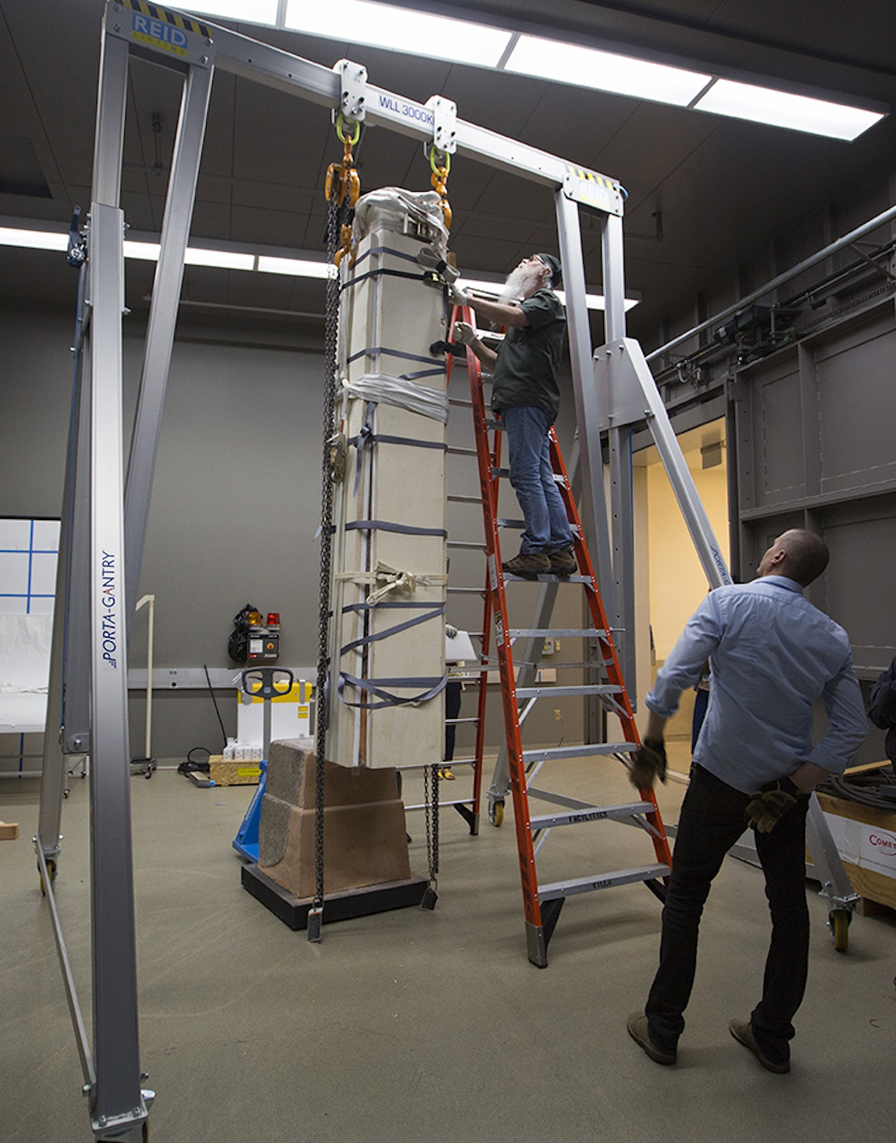 A man on a ladder checks the position of an obelisk that is standing upright in packing material