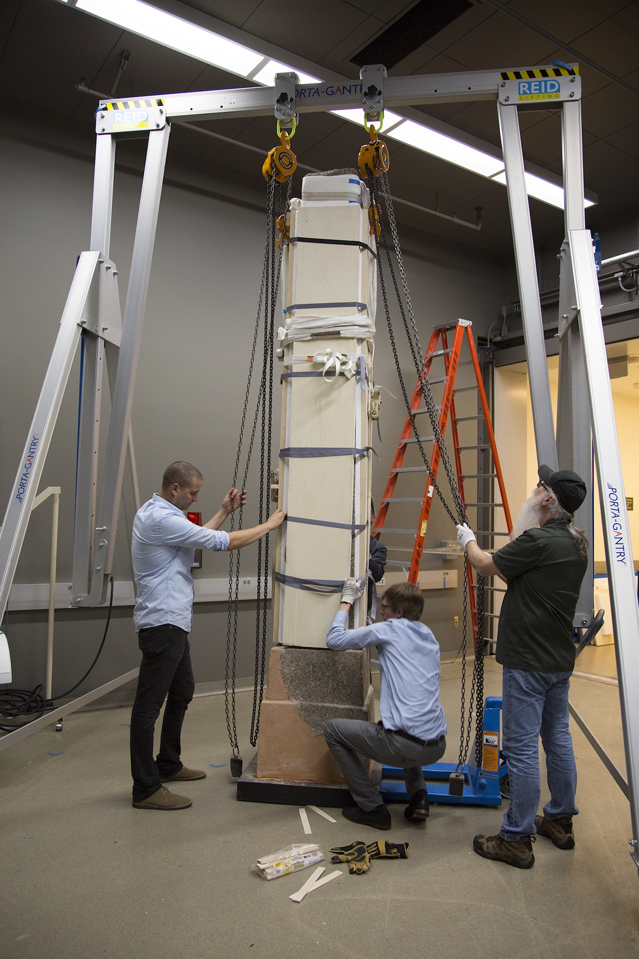 A stone obelisk, still in its packing materials, is gently guided onto its base by three men in a large, fluorescent-lit room