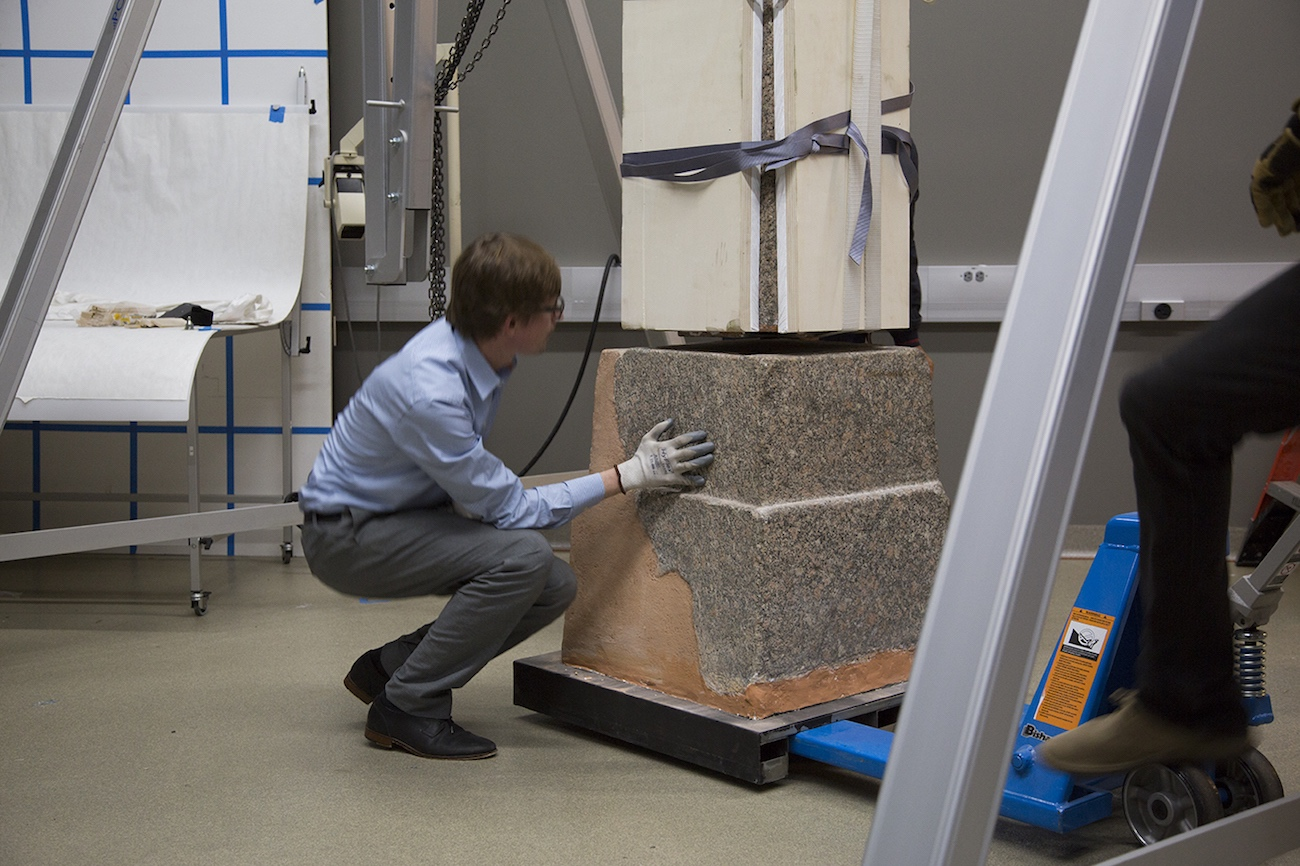 Close-up of an art conservator guiding a stone obelisk onto its base