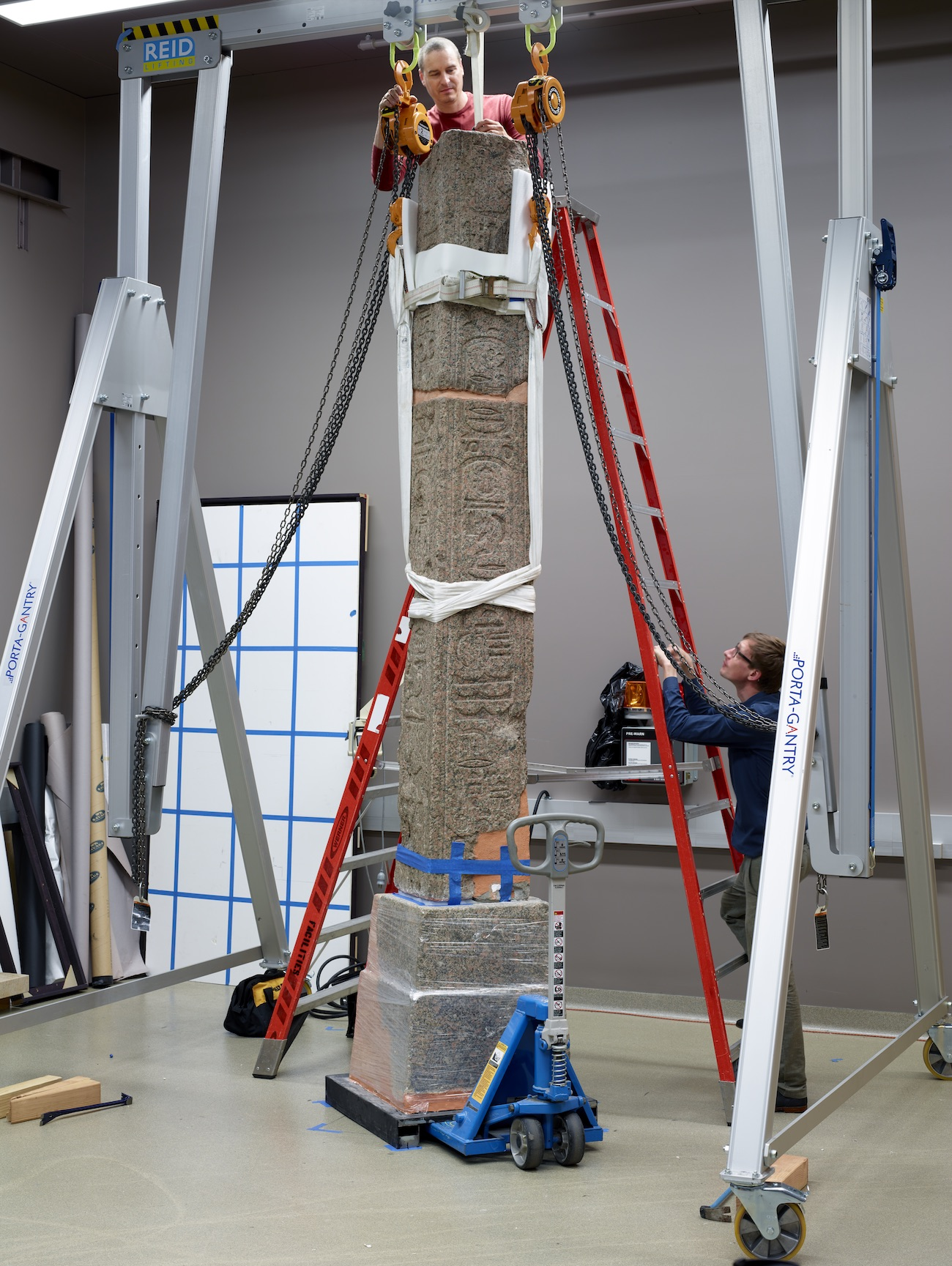 An obelisk stands upright in a conservation studio, held safely by ropes and mechanical equipment