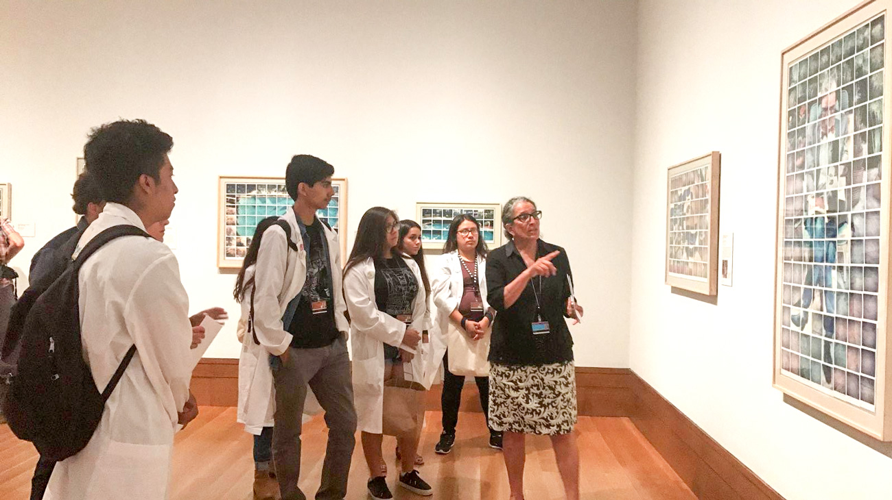 A group of teens in lab coats look at a framed painting while an adult talks and points to it.
