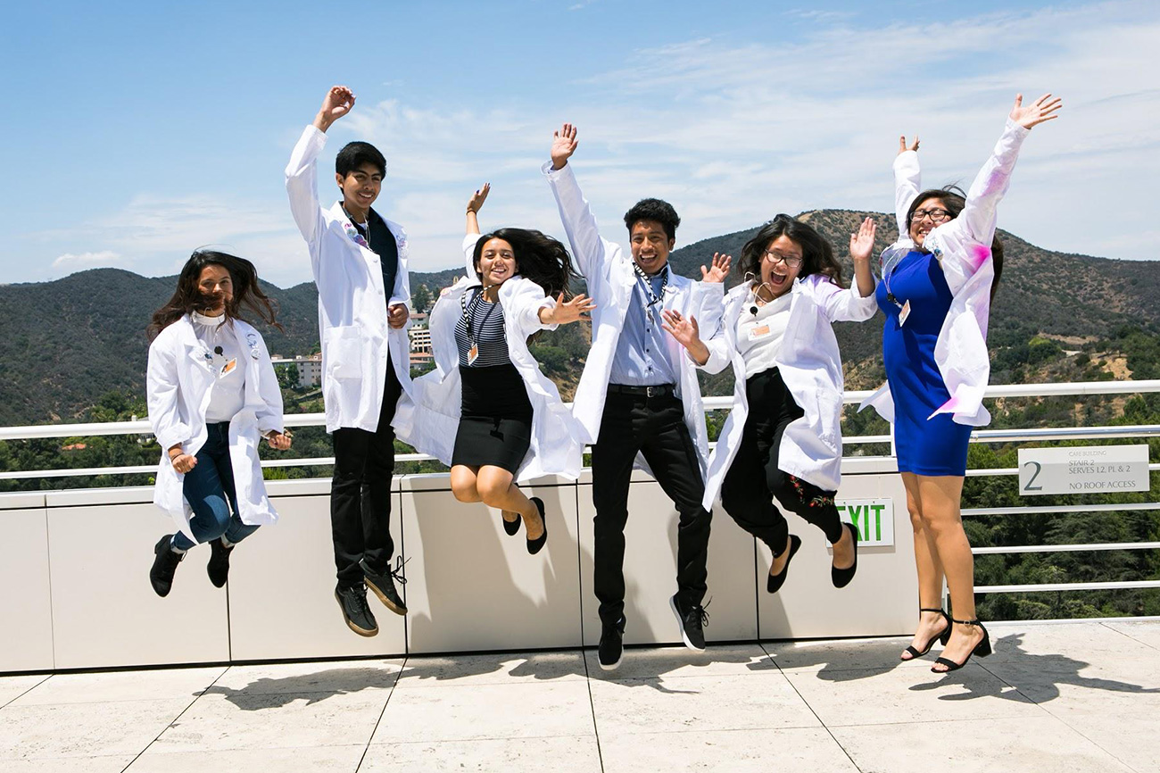 Six teens in lab coats jump in the air at the Getty Center overlooking the Santa Monica mountains.