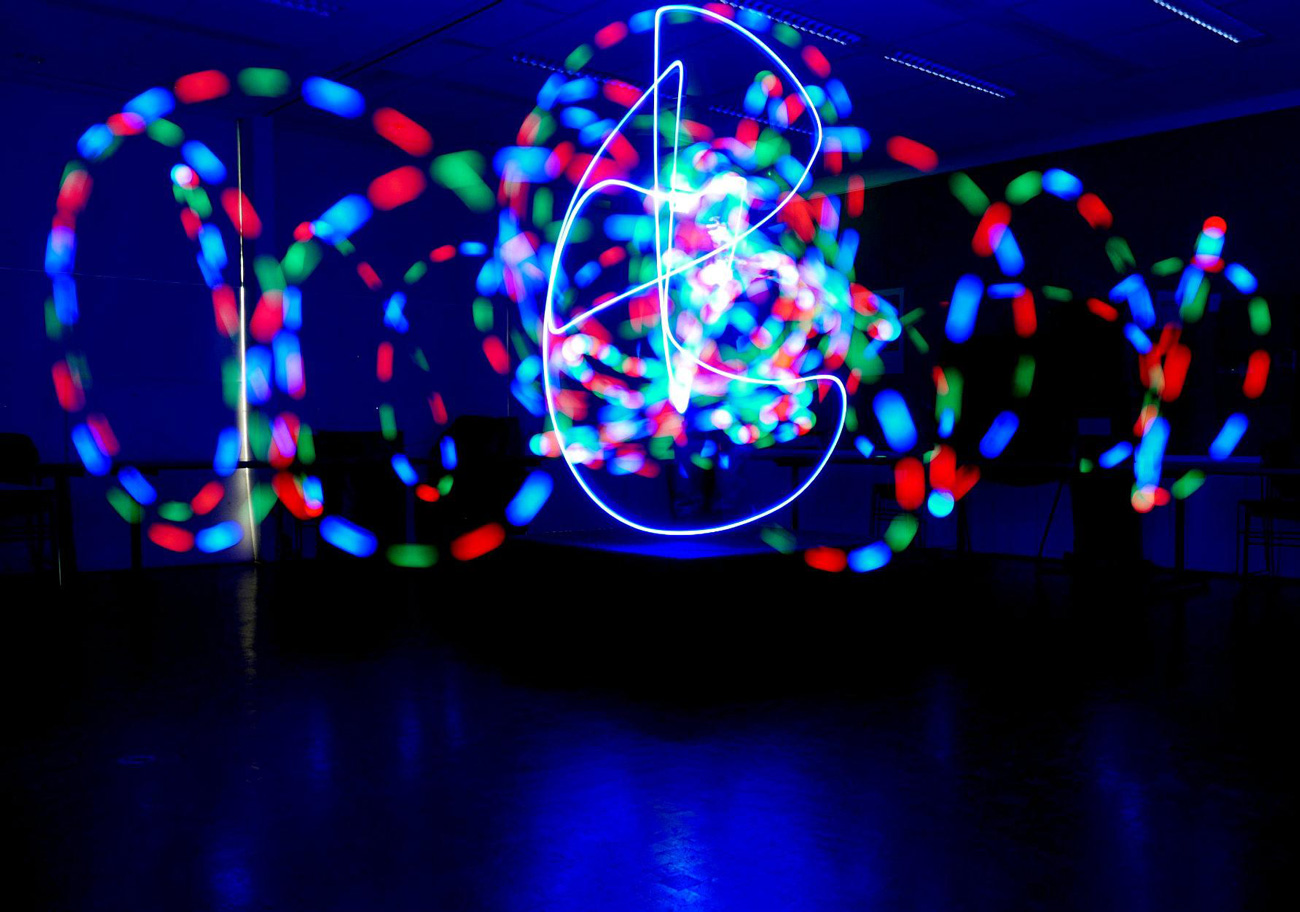 Intertwined spirals of light appear to be an abstract design but on closer inspection, are a long exposure of lights in motion in a dark room.
