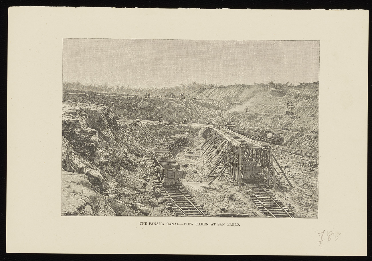 A black-and-white photograph of the construction of the Panama Canal shows carts full of rocks and dirt on rails in the middle of an area that has been dug out from the earth.