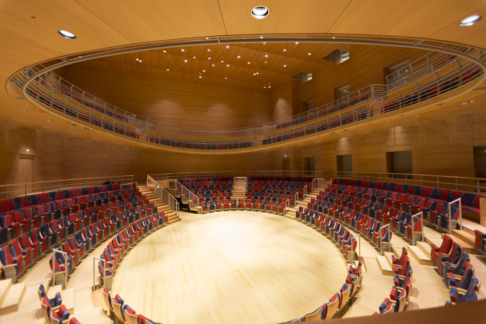 Seats circle a stage space in a wooden room. An upper level appears through an oval opening in the ceiling.
