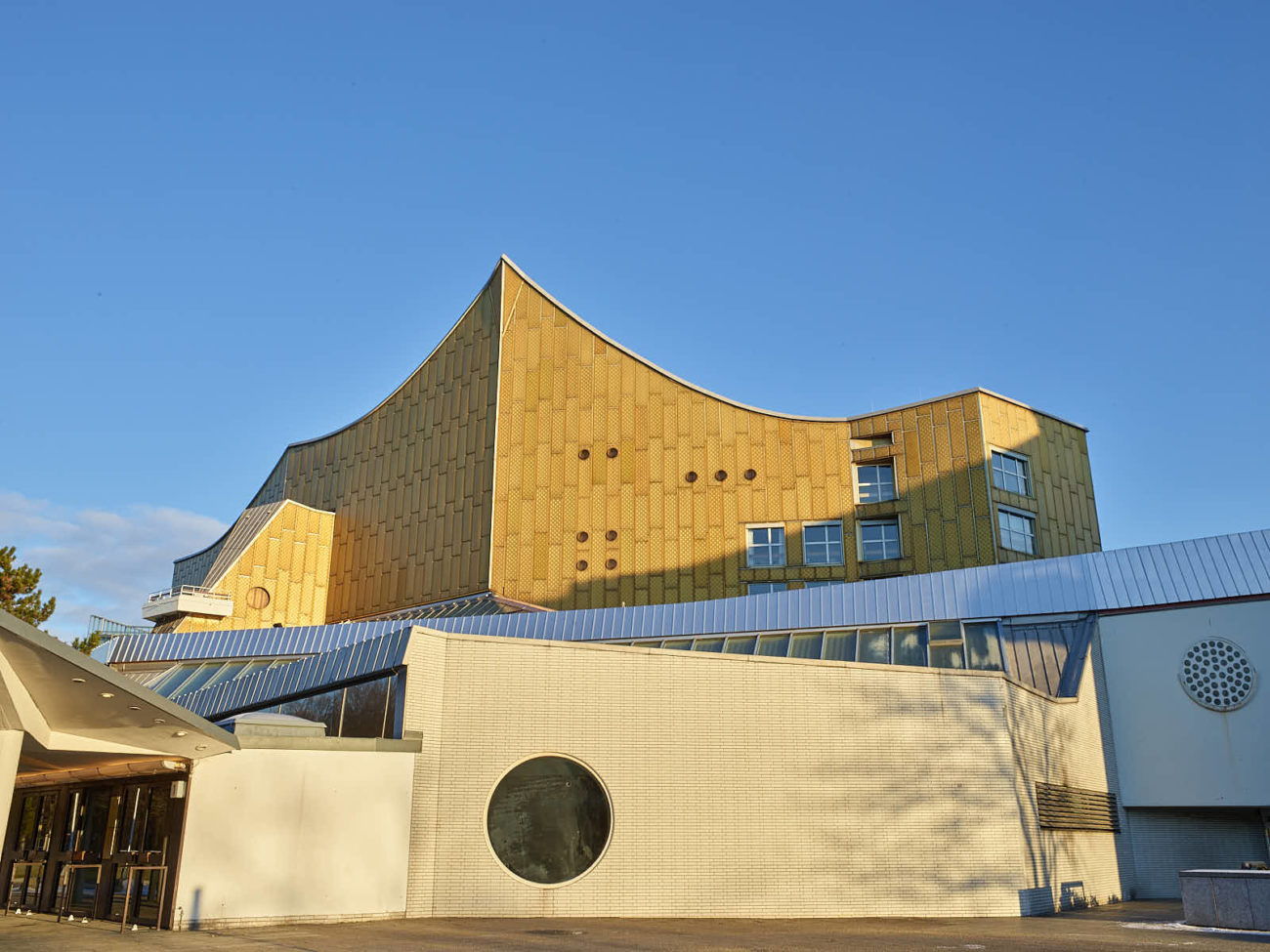 Exterior of a large angular building clad in brick, glass and large rectangular tiles, under a blue sky.