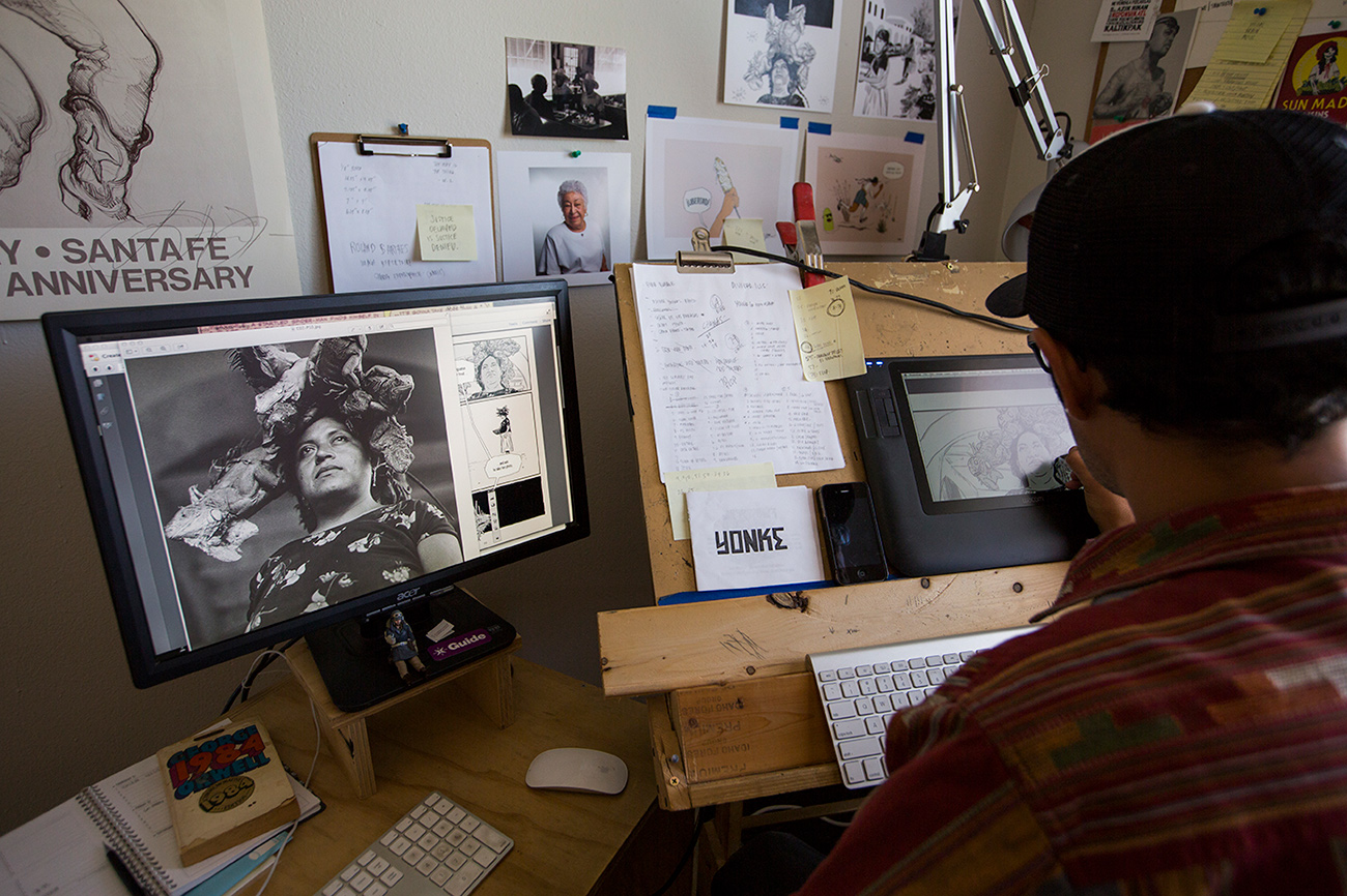 An artist has his back toward the camera drawing on a tablet from a photograph enlarged to his left on a computer monitor.