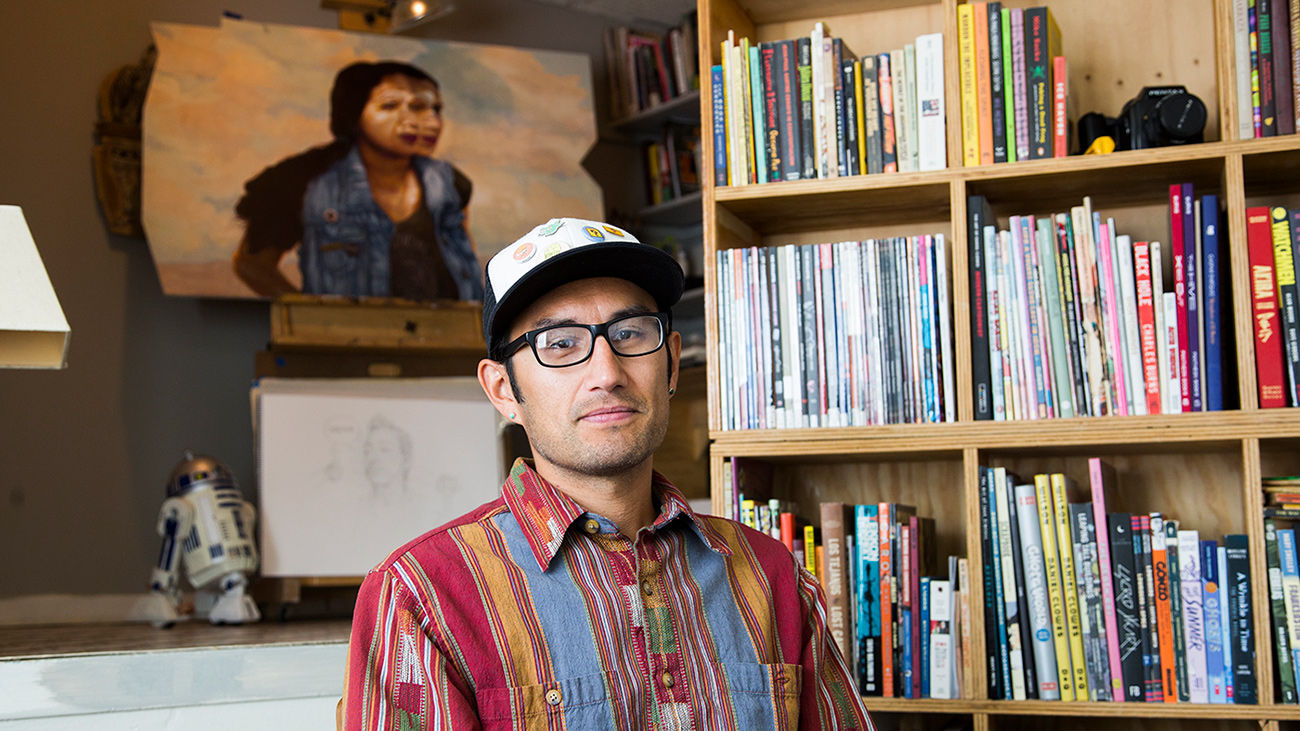 Artist and illustrator Zeke Pena sits in his studio, looking at the camera. He is wearing a colorful red, orange and blue shirt, a baseball cap and black framed glasses.