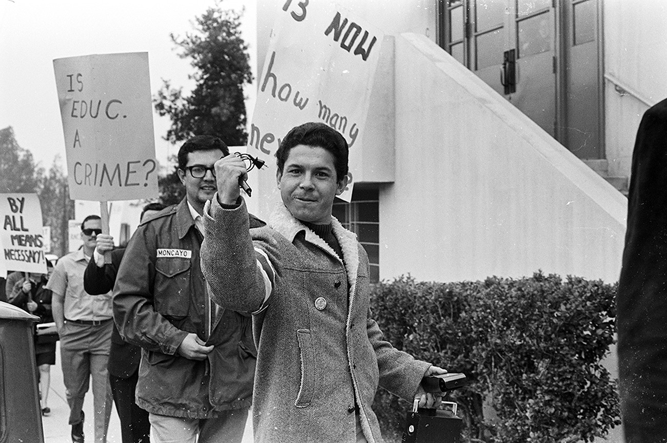 Black and white photo of young adults holding protest signs. At center, a man raises a fist and makes eye contact with the camera