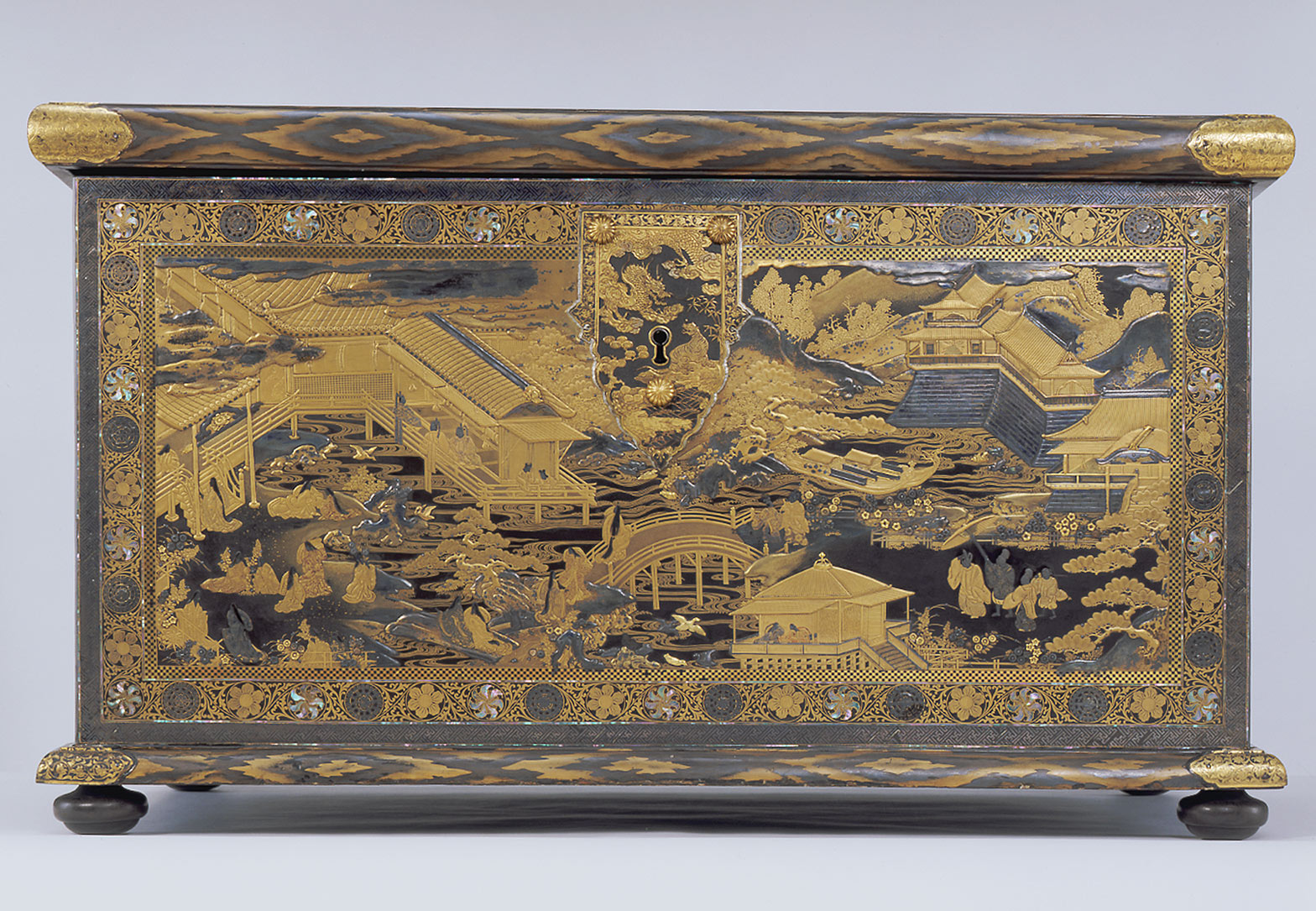 A rectangular Japanese chest covered with detailed lacquer in black and gold