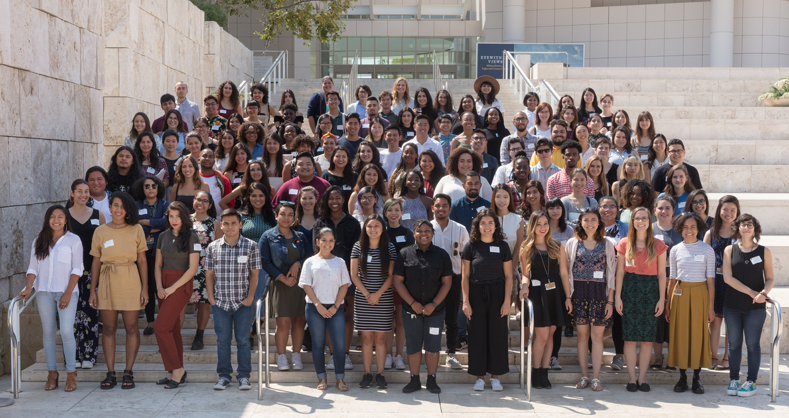A large group of college students of color pose facing the camera on the steps of the Getty Center