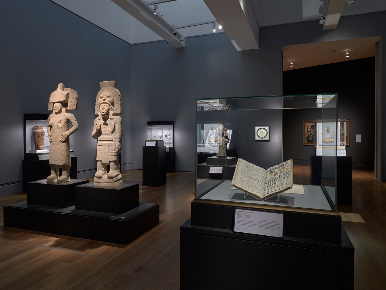 Installation view of Golden Kingdoms featuring an open codex and two stone sculptures of people in ritual regalia.