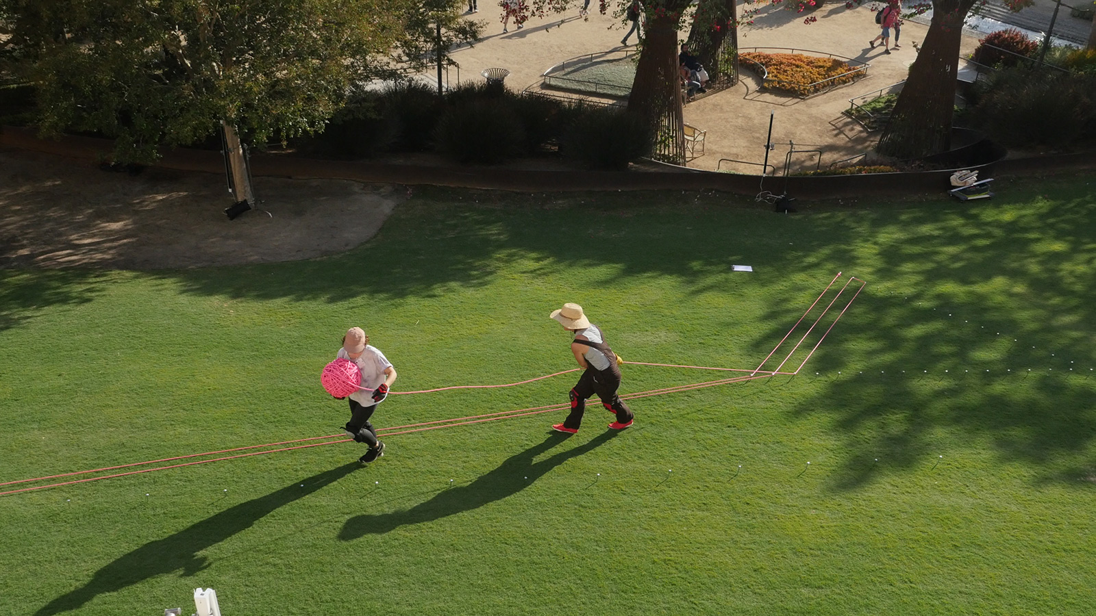 Overhead view of two women on a large lawn, unspooling a large spool of bright pink rope