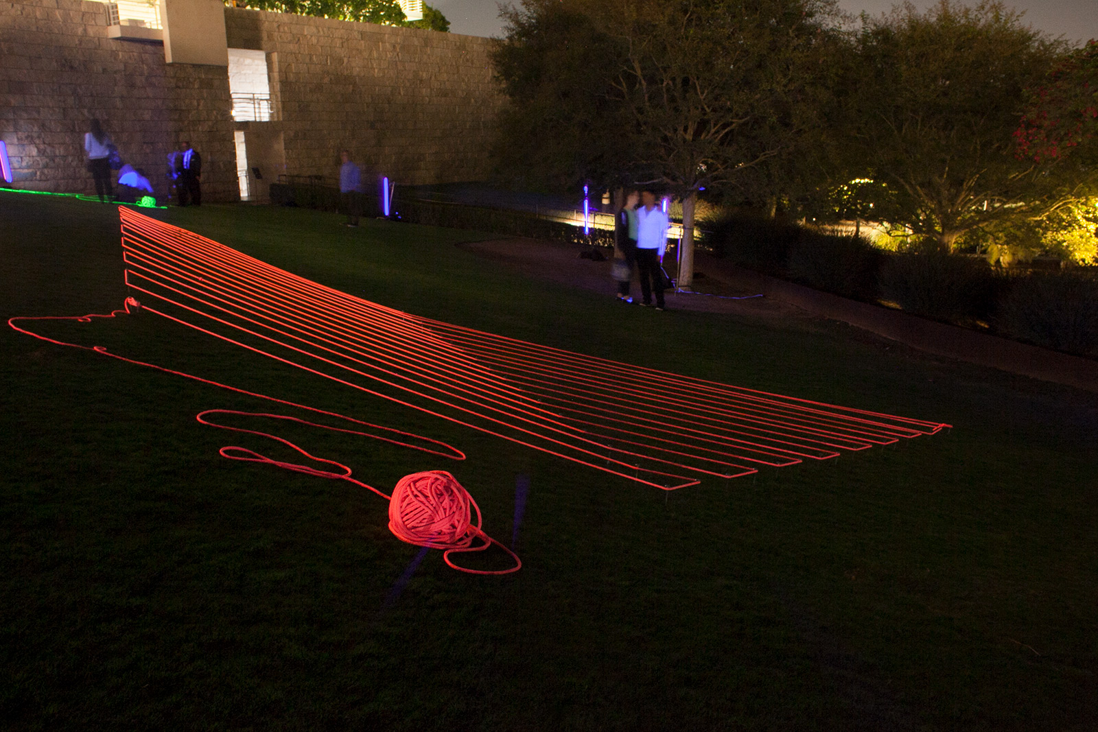 Nighttime view of a large lawn with bright pink glowing rope arrayed in parallel lines