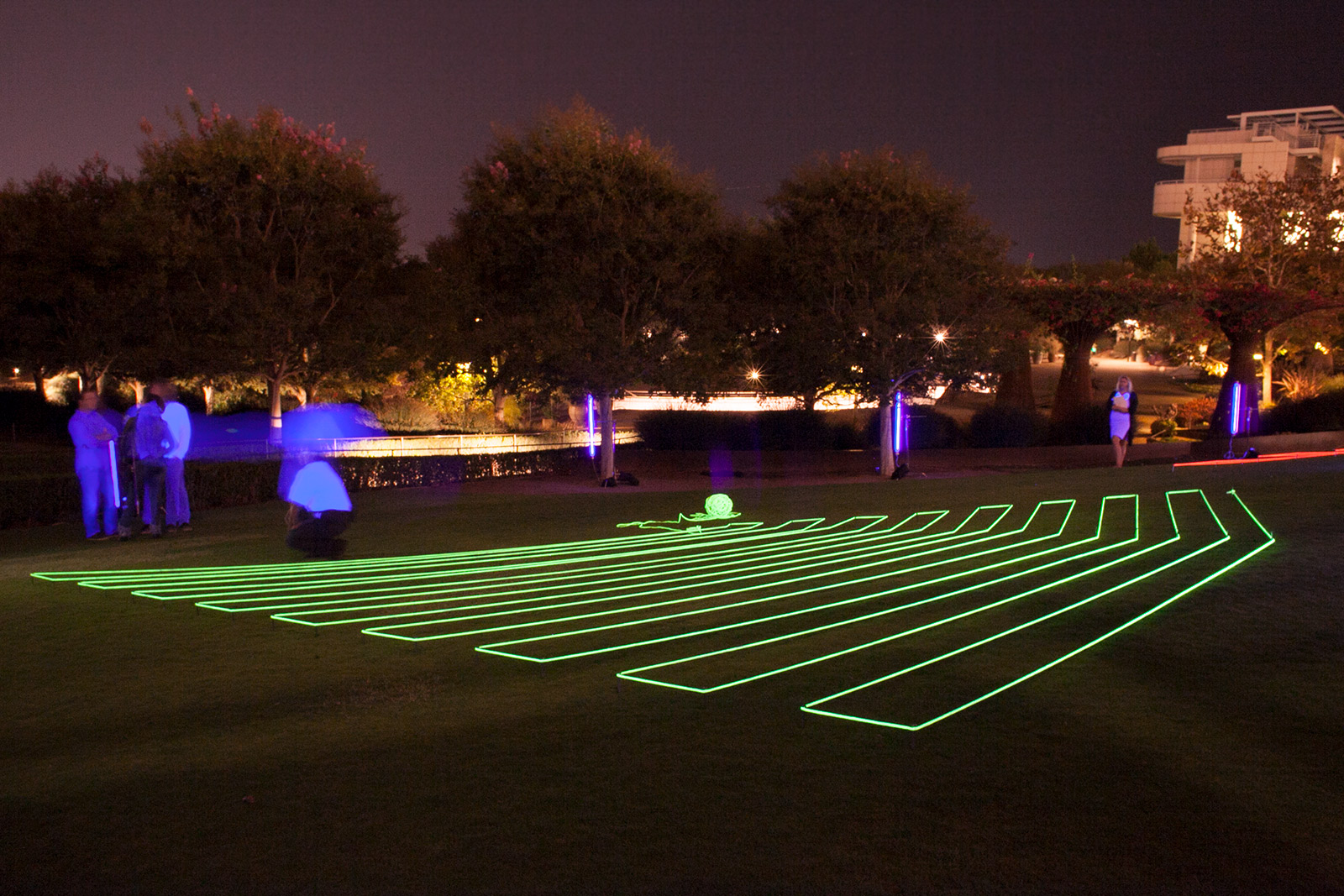 Nighttime view of a large lawn with thick, fluorescent-glowing rope arrayed in a geometric pattern