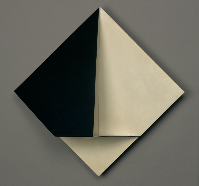Front view of a black and white, geometric, sculptural painting that juts out in the center from the wall