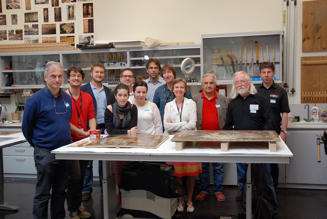 A group of conservators stand behind a table with two old master panel paintings, smiling at the camera