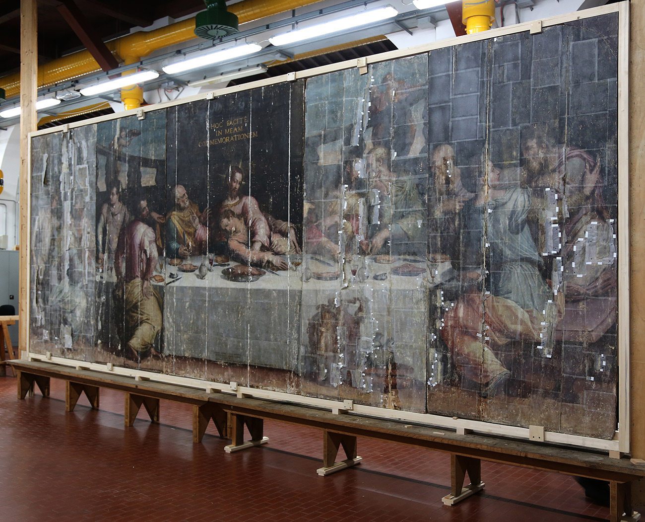 Oblique view of a large, tattered painting on a stretcher in a conservation studio