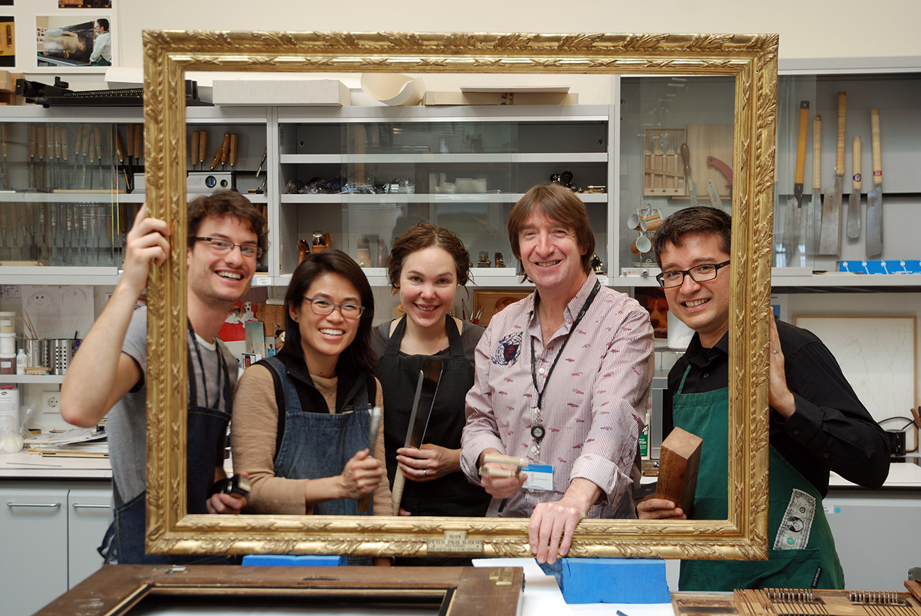 Five conservators in an art-conservation lab face the camera, smiling as they hold up a large gold picture frame