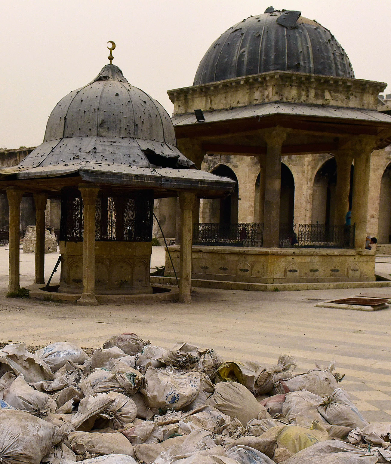 Sandbags fill the foreground of this scene of war ruins of a historic mosque