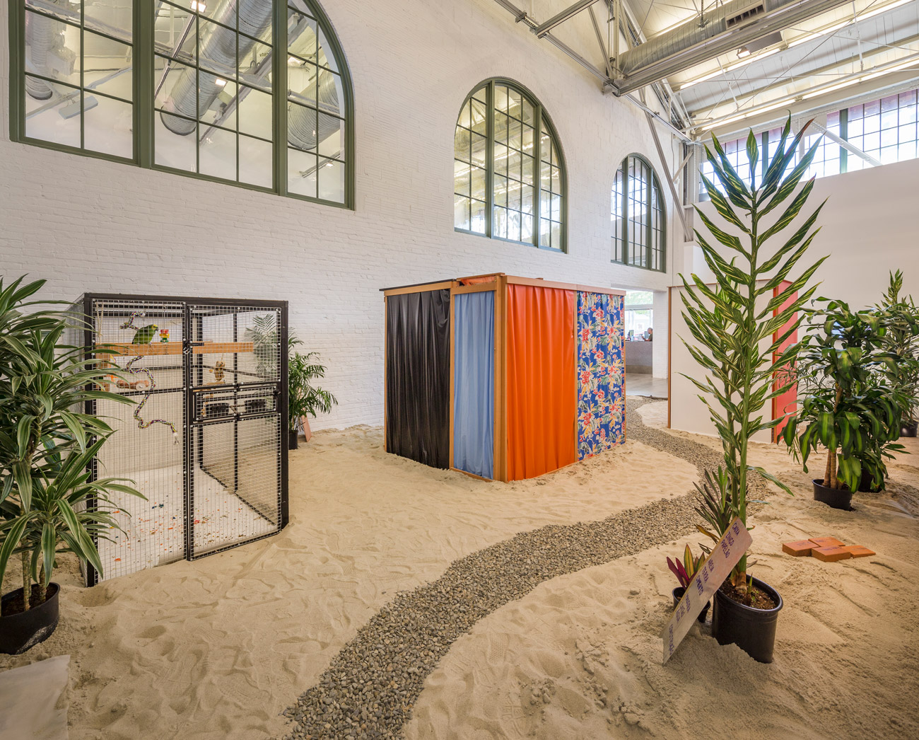 In a large room, sand covers the floor and a gravel path winds through objects including potted trees, a bird cage, a small structure draped in fabric and a handwritten sign.