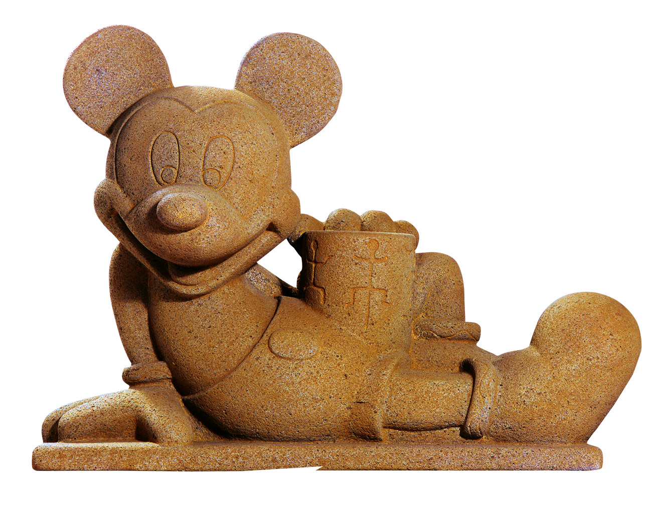 A stone sculpture of a grinning, reclining Mickey Mouse that blends Disney imagery with Aztec forms