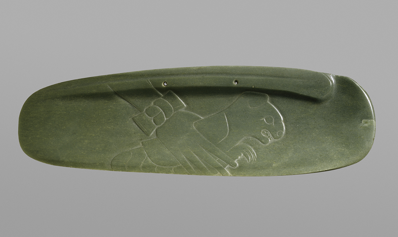 A rectangular piece of jade with rounded edges with a faint carving of a hand holding a feline creature.