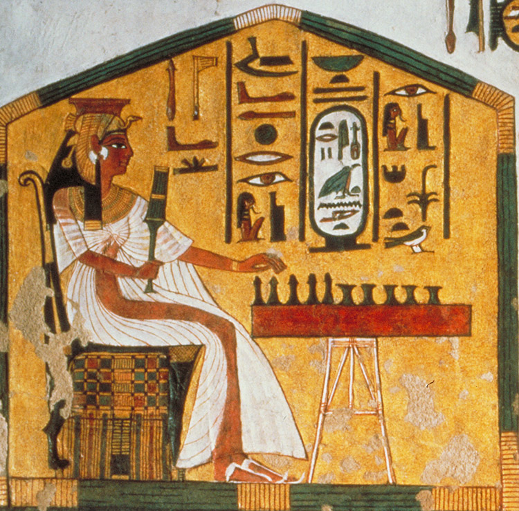 Flaking fresco of a woman in a white dress and sandals with a vulture headdress and scepter. She reaches forward to play a game on a table. Hieroglyphs surround her.