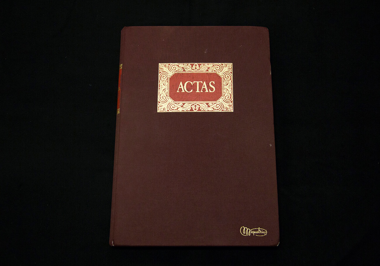 A closed book with gilded lettering reading ACTAS.