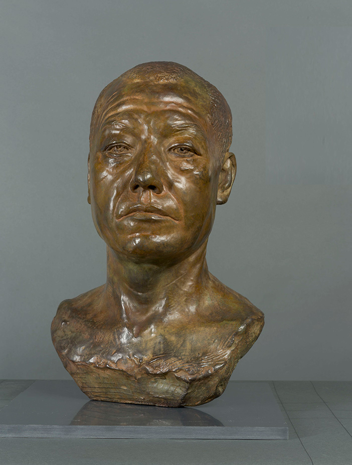Bronze bust of a vaguely Oriental-featured man with heavy lids, looking past the viewer with a heavy stare