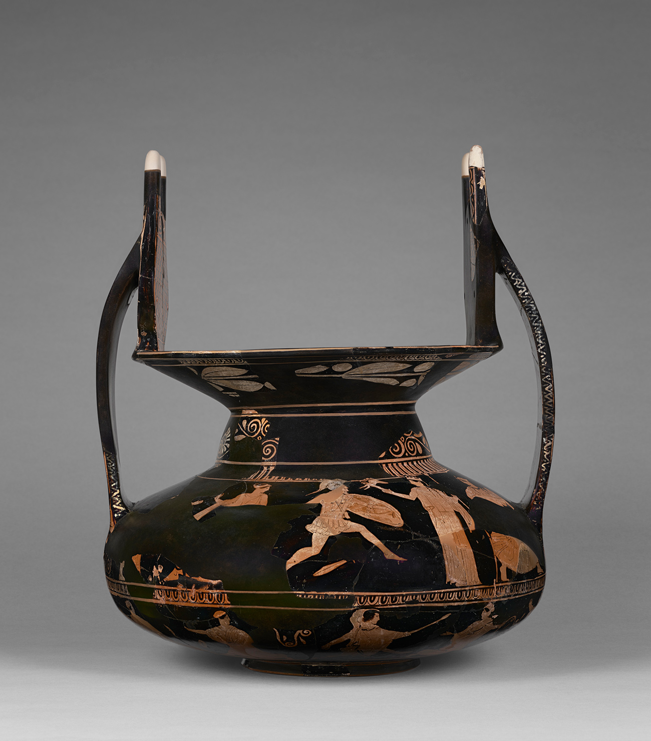 An ancient terracotta vessel, painted black with orange figures, has dramatic upswung handles