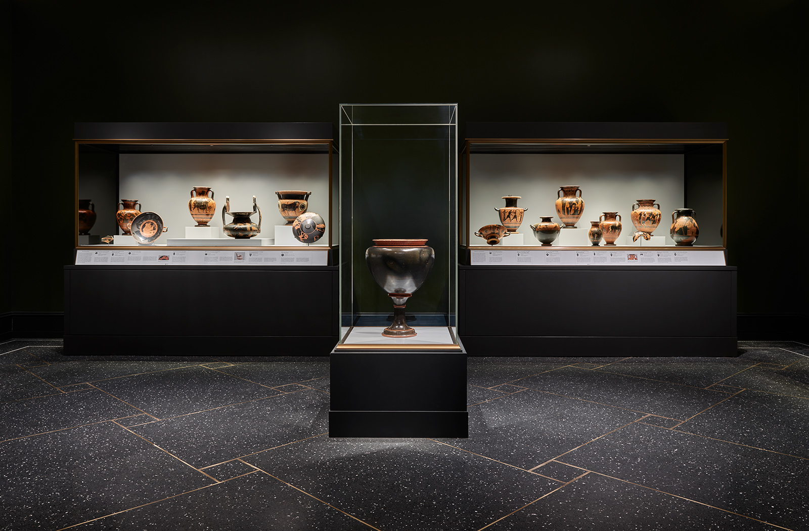 A darkly lit museum gallery with glass cases holding ancient Greek terracotta vessels