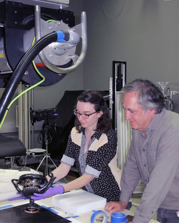 Julia Commander wears gloves to position the kantharos under the overhead X-radiograph machine. To her right is conservator Jeff Maish.
