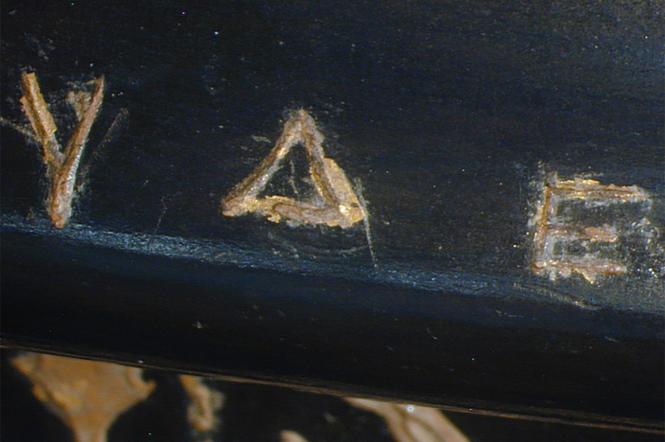Light incision marks outlining letters in the description are visible under and next to the gilt letters on the rim of the cup.
