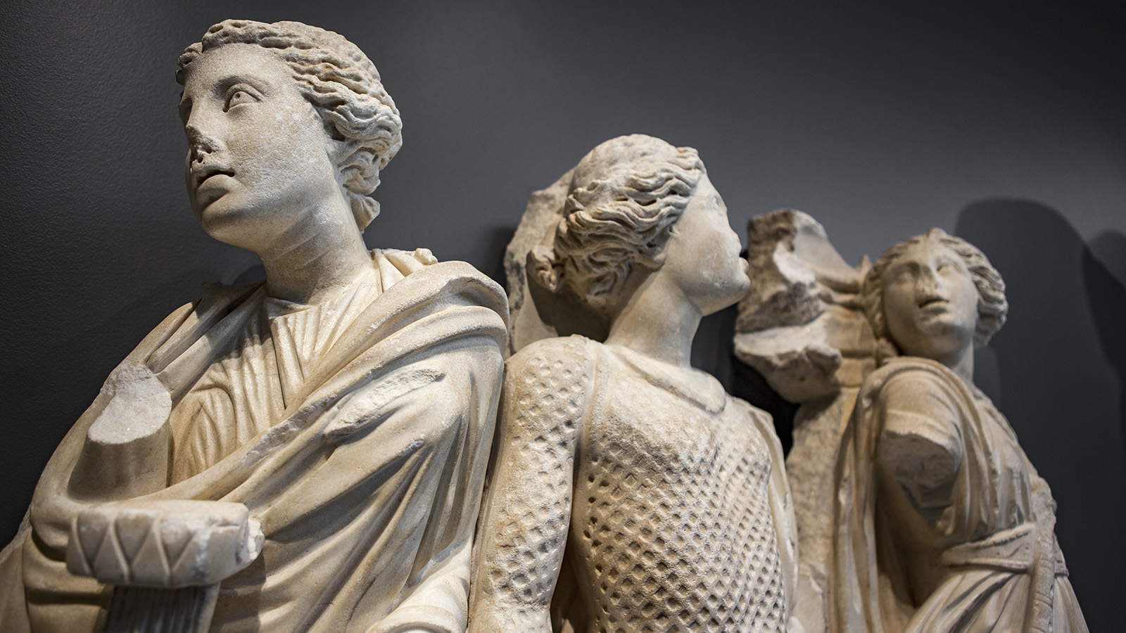 Close Up Detail Of The Faces And Torsos Of Three Muses Sculpted In White Marble