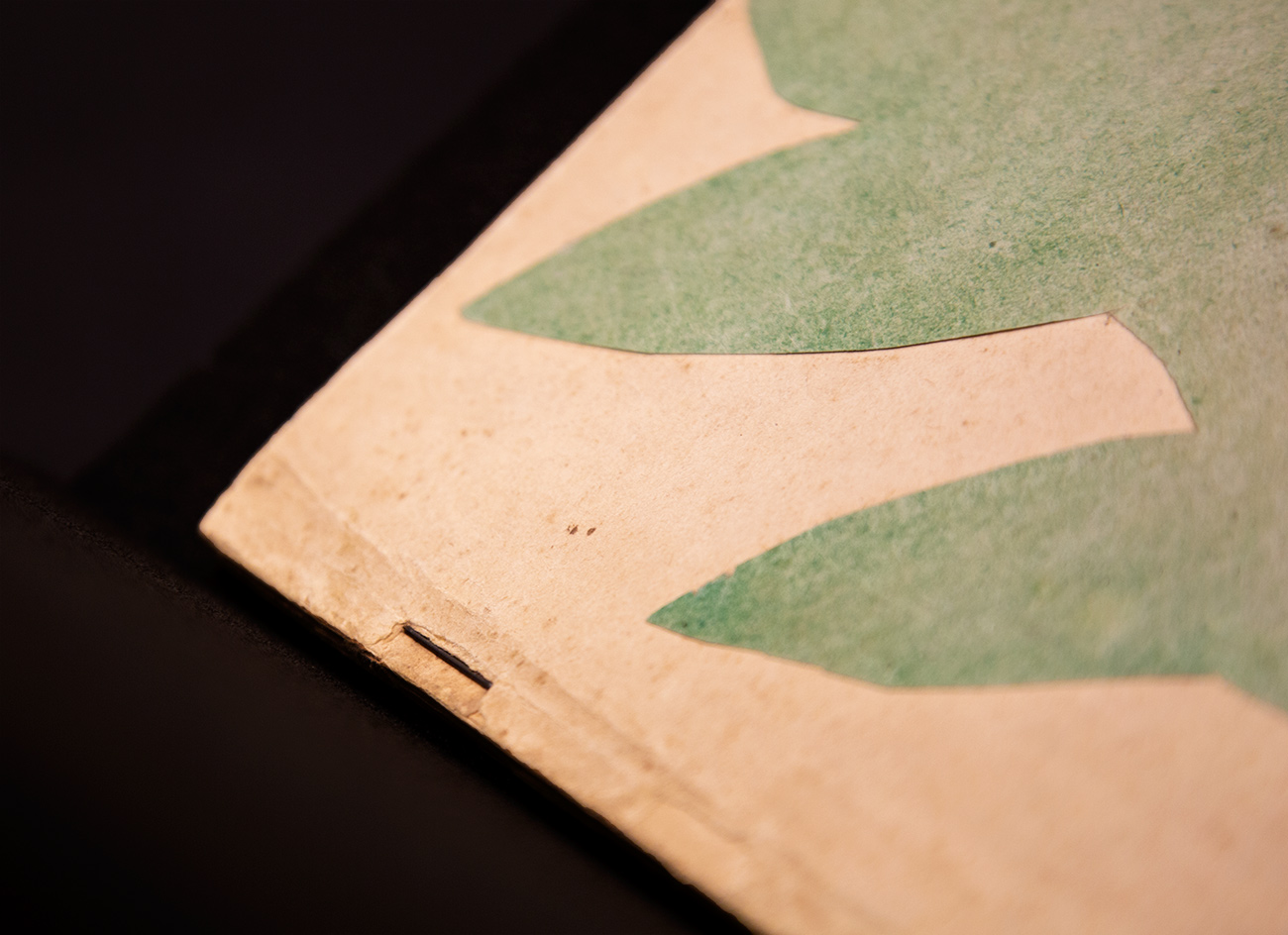 Close-up view of a handmade book showing how collaged green paper is affixed to the cover page below