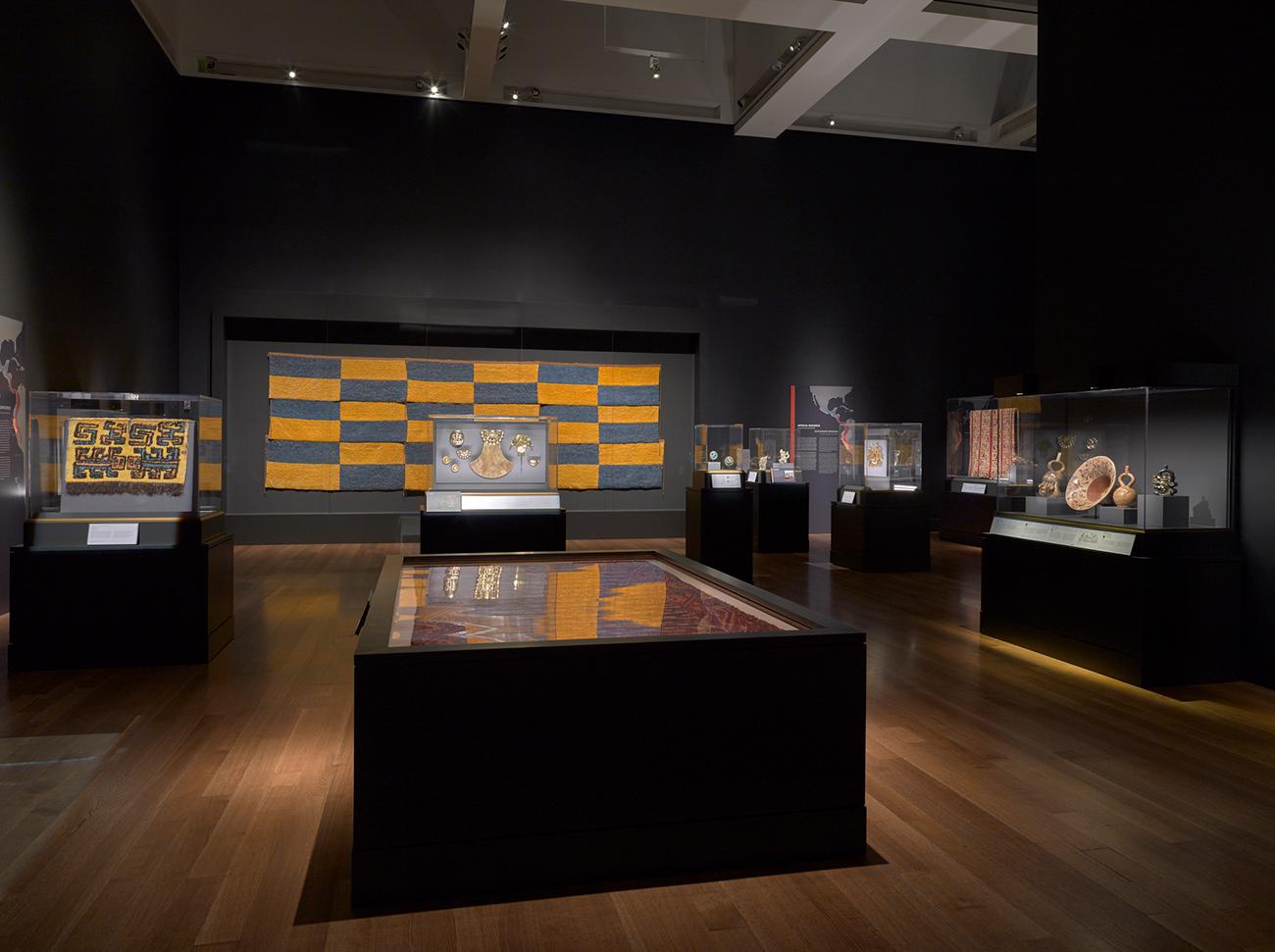 Vista de la instalación de Golden Kingdoms (Reinos del oro), mostrando paneles emplumados, objetos de oro y cerámica.