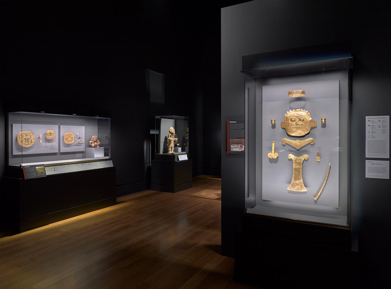 Vista de la instalación de Golden Kingdoms (Reinos del oro), mostrando relieves dorados iluminados de forma dramática en un cuarto oscuro.