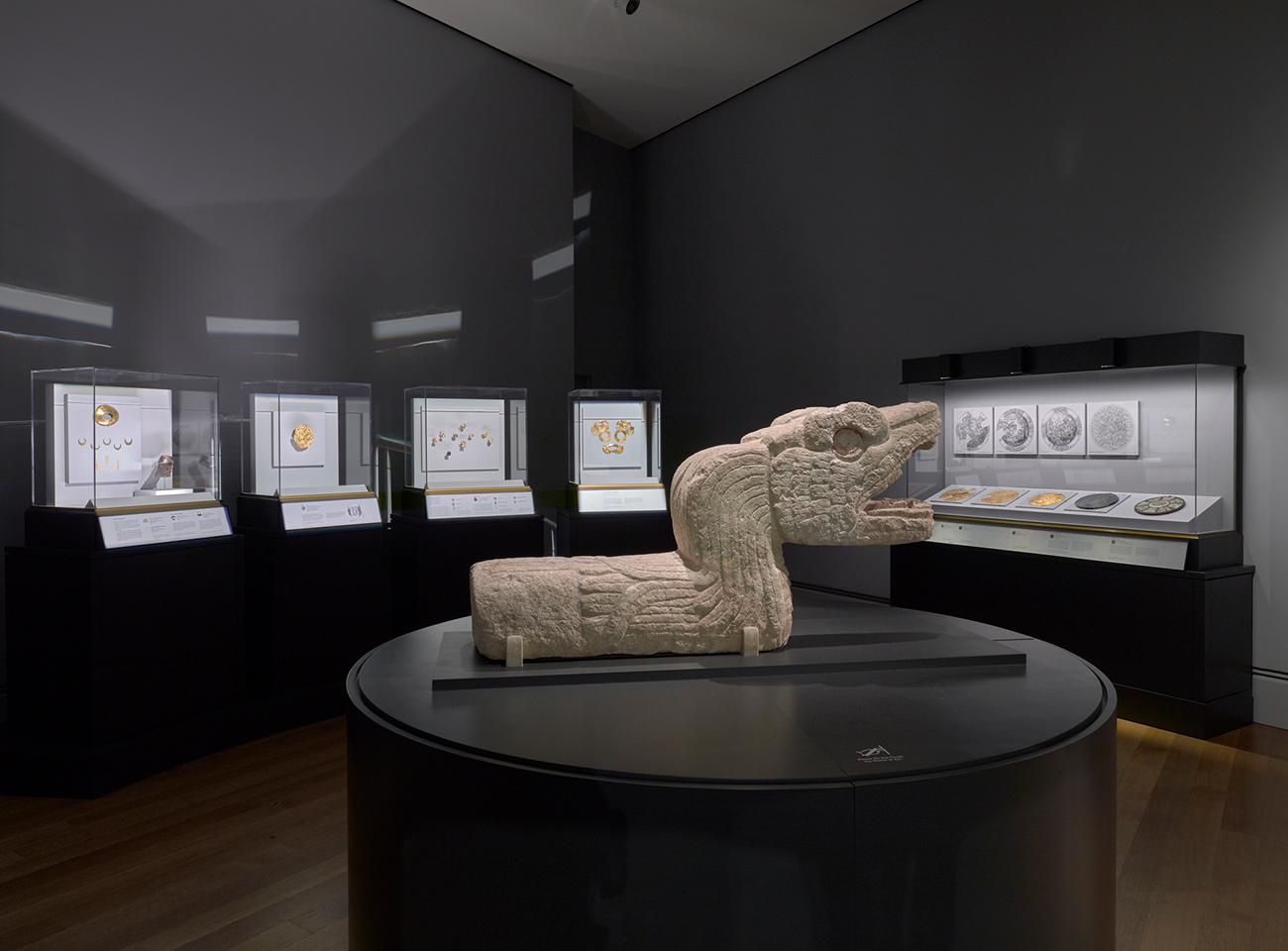Gran escultura de piedra de una serpiente emplumada con numerosos artefactos más pequeños de metal al fondo.