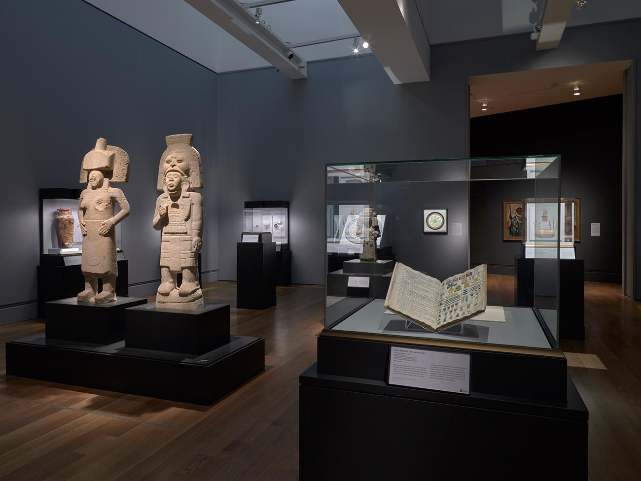 Vista de la instalación de Golden Kingdoms (Reinos del oro), mostrando un códice abierto y dos esculturas de piedra de personajes con vestimentas rituales.