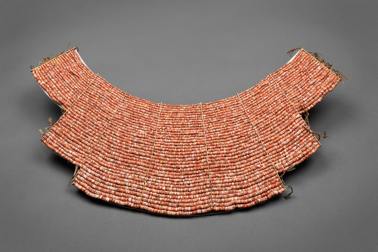 An ornate neck piece is made of tiny orange-red shells that look like small beads.