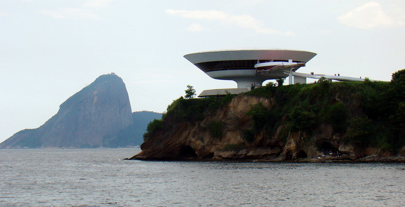 Futuristic disc-shapped white museum sits on top of a cliff overlooking a body of water.
