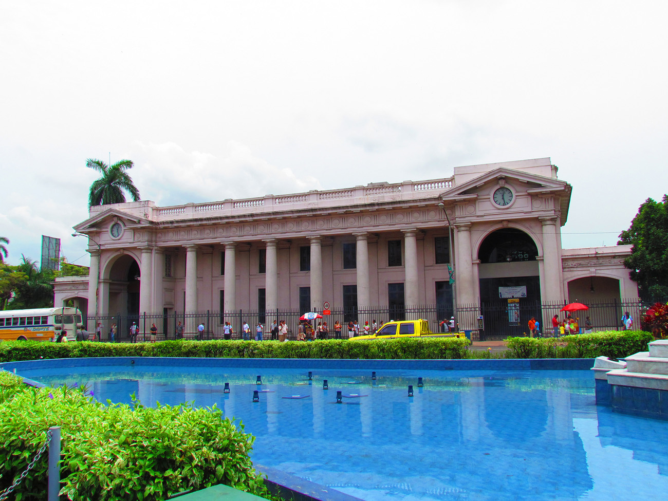 Large neo-classical style white building in Panama. The building is in front of a fountain that is turned off in the photo.